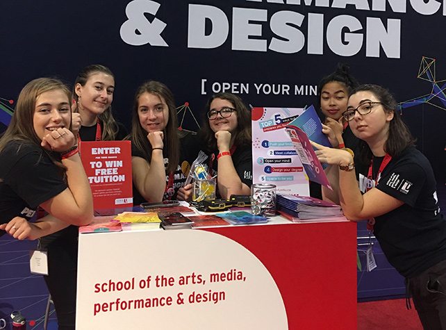"Six student ambassadors pose around a table labeled ""school of the arts, media, performance & design"""