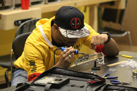 young man soldering a gadget