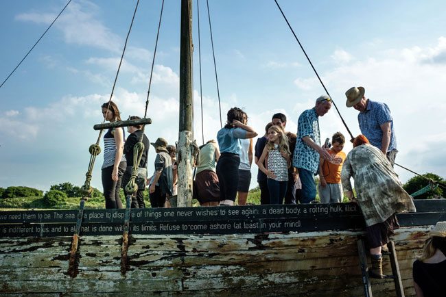 A group of people climb up and stand on an old fishing boat that is lodged in a salt marsh, and is inscribed with memories of lost things