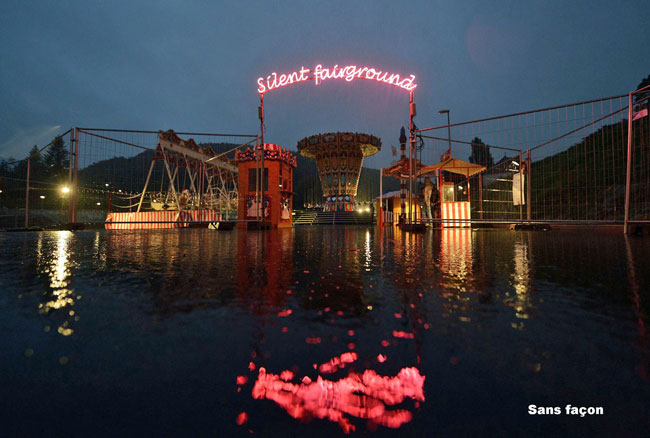 Night-time image of a carousel and fairground attractions reflected in a body of water