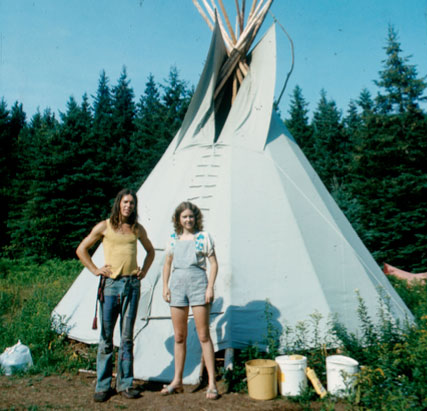 Vintage photo of a white couple standing in front of a tee-pee