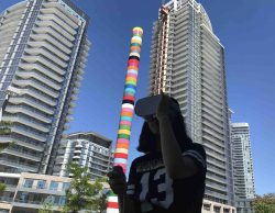 Image of a woman holding a virtual reality headset with her left hand. Behind her are two tall condominiums and between them stands a tall, multicolour poll.