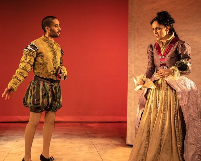 Two actors in renaissance garb stare at eachother onstage.